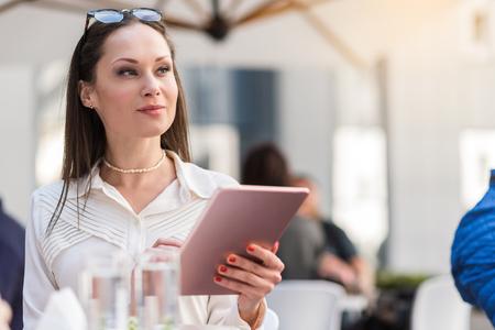 Pensive female having job with digital device