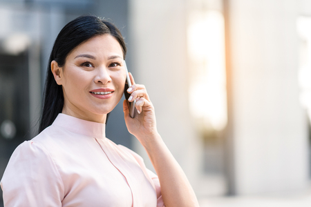 Outgoing woman telling by mobile Stock Photo