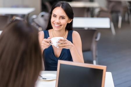 Outgoing female tasting mug of beverage