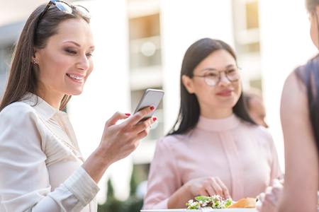 Beaming female watching at phone in cafe Stock Photo