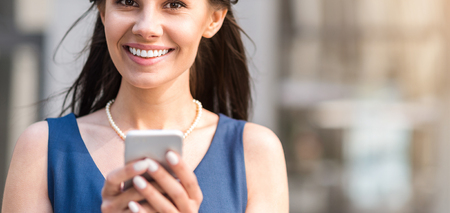Cheerful lady inscribing sms by mobile