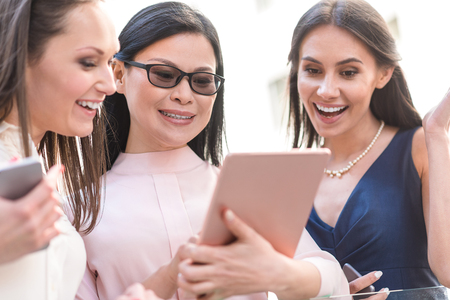 Outgoing females looking at electronic tablet Banco de Imagens