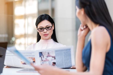 Pensive female looking through article