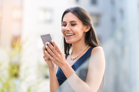 Happy woman sending sms by phone