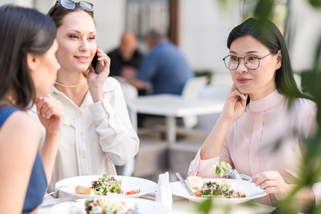 Pensive female eating dish in cafe Stock Photo