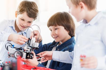 Vrolijke kinderen die robot houden Stockfoto