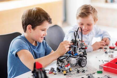 Gelukkige glimlachende jongens die pret in workshop hebben Stockfoto