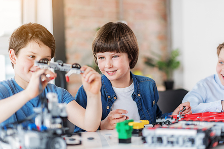 Interested smiling children making technical toy Stock Photo