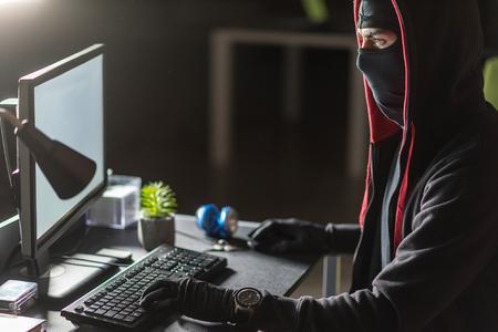Composed hacker stealing data at desk