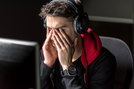 Serene exhausted male rubbing face at desk Stock Photo