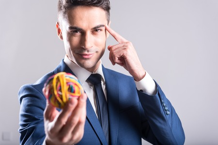 Cheerful male holding little colorful ball