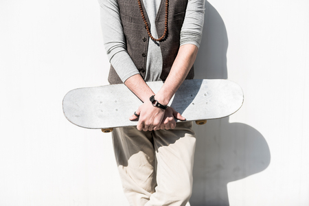 Young stylish guy is standing with board