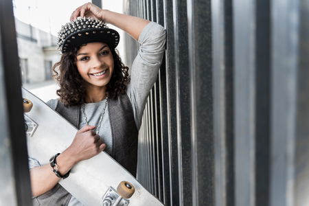 Happy stylish girl is laughing while leaning on fence Stock Photo