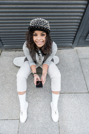 Positive teenage girl is sitting outdoors Stock Photo