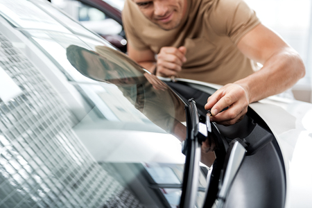 Cheerful male examining technical equipment of car Stock Photo