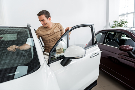 Outgoing man touching automobile in shop Imagens