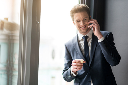 bristles: Cheerful young man drinking coffee while having conversation on smartphone Stock Photo