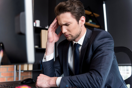 Depressed young man is having headache Stock Photo