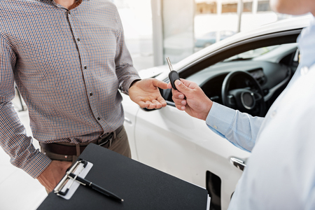 Man taking clef of automobile from salesman