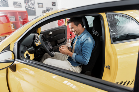 Outgoing man typing sms by phone in car