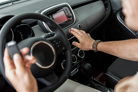 Male hand pushing emergency switch in car Stock Photo