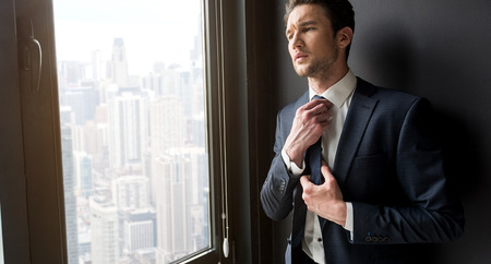 Stylish pensive man is standing near window Stock Photo