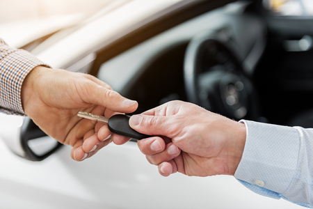 Buyer arm taking automobile clef from salesman