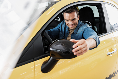 Happy male correcting side mirror in car