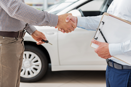 joining: Salesman and buyer joining arms near automobile Stock Photo
