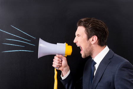 Grumpy businessman is yelling through bullhorn Imagens - 80169089