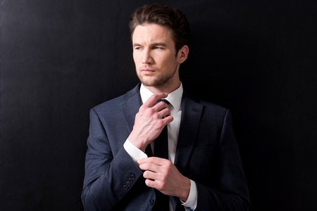 Elegant man in suit is posing pensively