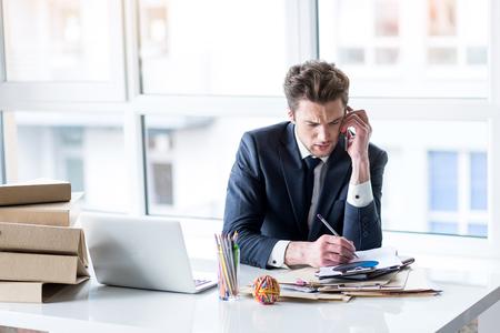 Homme déprimé en costume parle sur smartphone Banque d'images - 80043562
