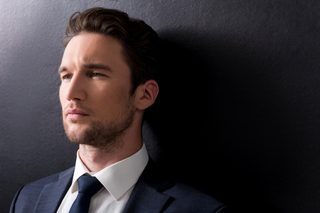 serious man with stubble is standing against dark background Stock Photo