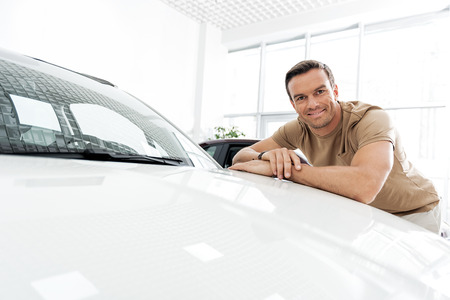 Cheerful male reclining on automobile hood Stock Photo