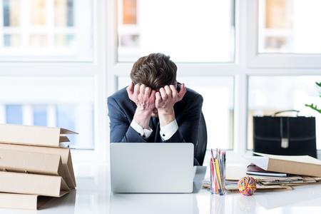 Jonge werknemer is moe van het werken op laptop