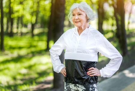 Jolly femme senior s'entraînant parmi les arbres verts Banque d'images - 80183522