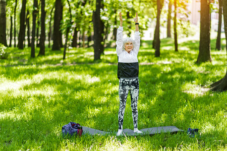 Jolly senior lady doing exercises outdoors on green grass Stock Photo