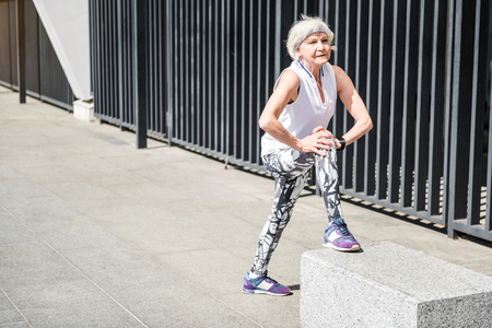 Serious old woman exercising on sidewalk near high metal fence Stock Photo