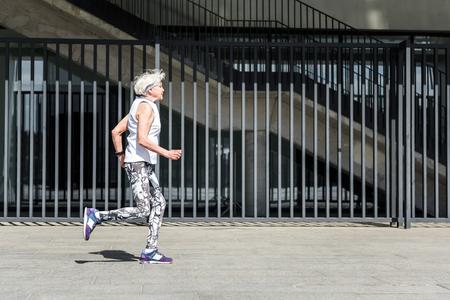 Solemn elderly lady training jogging near modern building outside