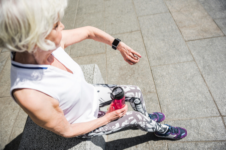 Elderly lady relaxing after sport activities outside building Stok Fotoğraf