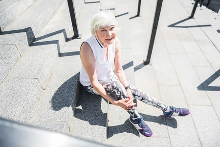 guardrails: Jolly elderly woman relaxing while exercising on stairs outdoor