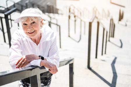 巨大な梯子建設で休んでうれしそうな年配の女性
