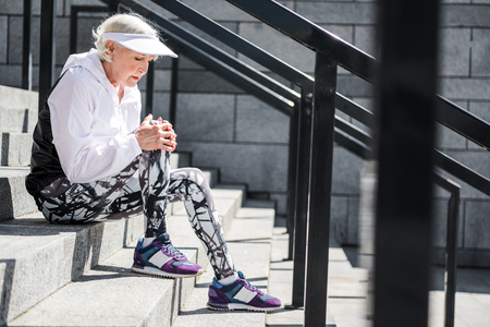Depressing aged woman having rest on stone stadium ladder