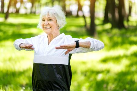 Happy senior woman training outside in park Stock Photo