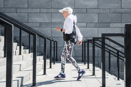 Solemn senior woman jogging outdoor on stone steps with handrails