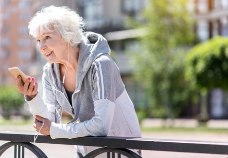 sidewalk talk: Happy old woman taking rest after exercise near fence Stock Photo