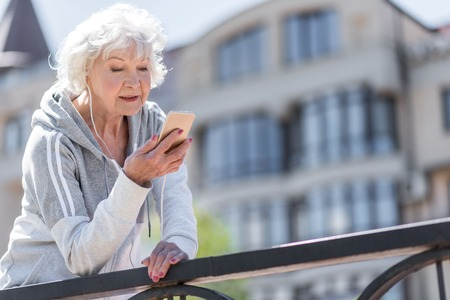 earbud: Happy nice elderly woman having relax time while exercising outdoors Stock Photo