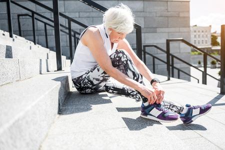 厳粛なシニア女性ブロック階段上の運動の準備 写真素材