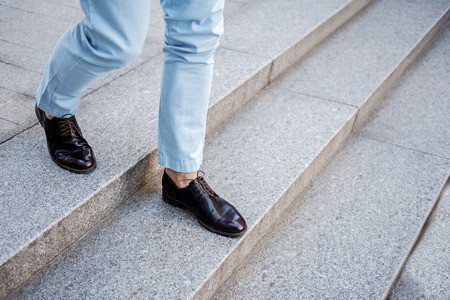 welldressed: Active stylish male person going on steps Stock Photo