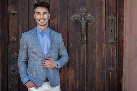 Cheerful smiling male person standing near entrance Stock Photo